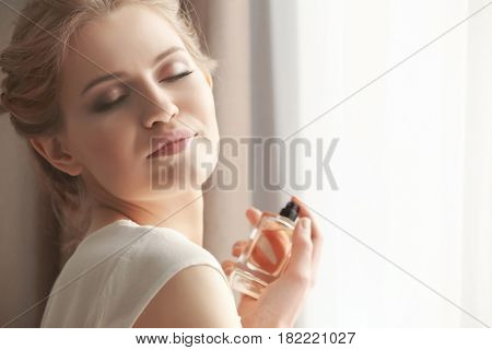 Beautiful young woman with bottle of perfume near window at home