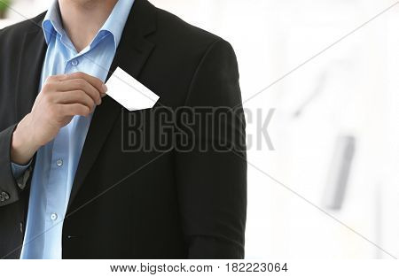 Young man with business card on blurred background, closeup
