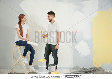 Young decorators painting wall in room