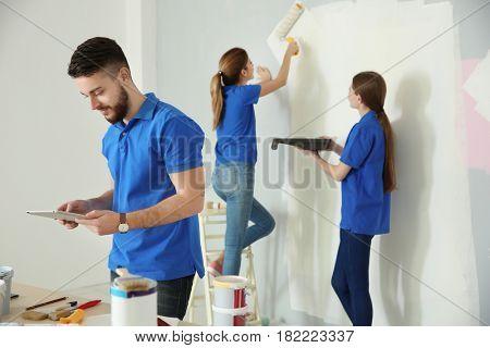 Team of decorators working in room