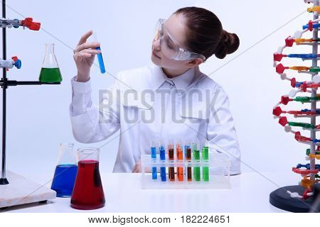 Happy school girl sitting at workplace and controlling chemical experiment, on light background