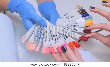 Nail technician shows the color palette of nail services in beauty salon. Woman selects of nail design.