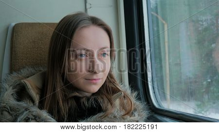 Close up shot of pensive woman relaxing and looking out of a train window. Travel, transport and winter concept