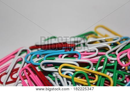 Colorful paperclips on white background. Miscellaneous office supplies. Assortment of stationery.