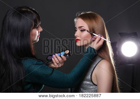 Backstage, fashion shooting. Make-up artist working with beauty model, applying eyeshadow, dark studio background