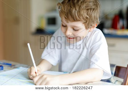 Portrait of cute happy school kid boy at home making homework. Little child writing with colorful pencils, indoors. Elementary school and education. Kid learning writing letters and numbers.