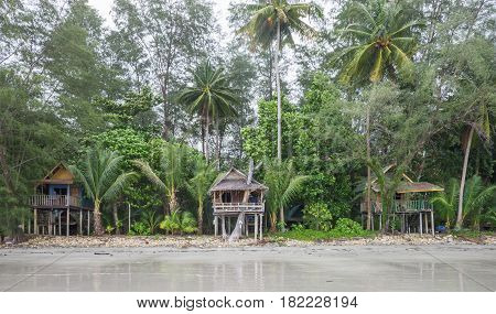 Beach on Koh Chang in Trat Province Thailand with trees and old beach huts on stilts.