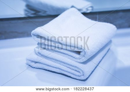 Two folded clean soft white absorbent cotton towels conceptual of the laundry and hygiene spa hotel or bed and breakfast