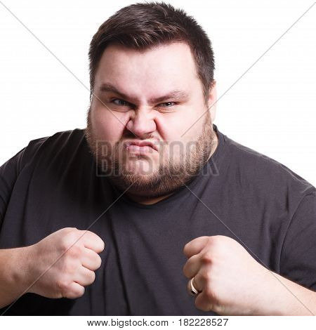 Feeling furious. Fighting fat man holding fists clenched, expressing anger, white isolated studio background