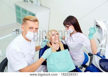 The dentist and assistant are treating  teeth to  girl.