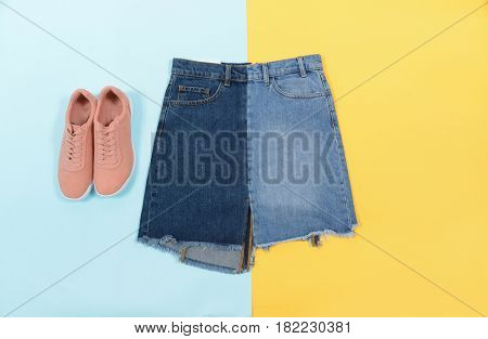 Blue denim skirt with shoe isolated on blue and yellow background