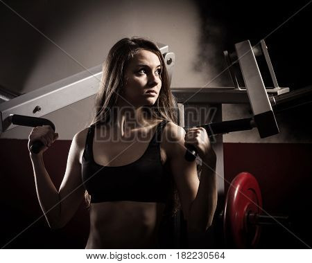 Young modern business woman at a fitness lesson in a modern fitness club.photo on a dark background