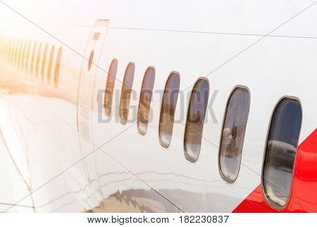 large heavy modern passenger widebody airplane side close up detailed exterior view with exit door handle, passenger windows, cargo door