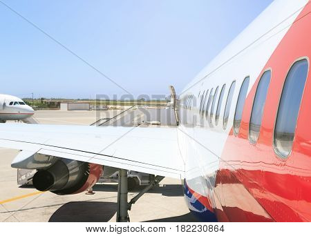large heavy modern passenger widebody airplane side close up detailed exterior view with exit door handle, passenger windows, cargo door