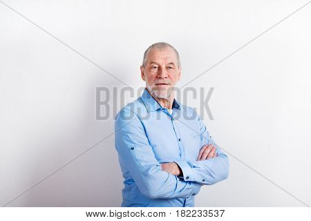 Handsome senior man in light blue shirt, arms crossed. Studio shot against white wall.