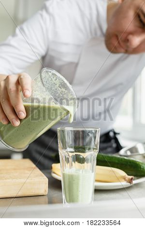 Young crop male in uniform pouring fresh smoothie of green color in clean glass.
