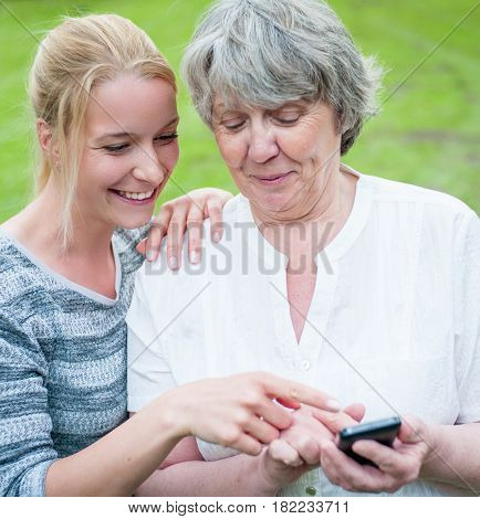 Young and old woman with smart phone outside in park