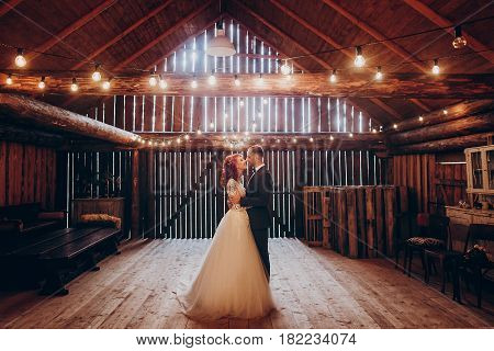 Stylish Groom And Happy Bride Hugging Under Retro Bulbs Lights In Wooden Barn. Rustic Wedding Concep