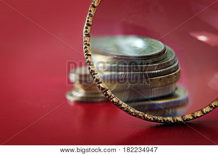 Capital increase magnifying glass in front of a small coin stack symbol for accurate check at financial investment red background with copy space selected focus narrow depth of field
