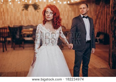 Stylish Groom And Happy Bride Posing Under Retro Bulbs Lights In Wooden Barn. Rustic Wedding Concept