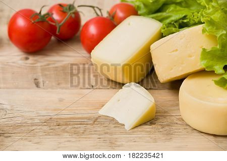 Cut cheese heads on wooden board served with tomatoes and fresh salad. Serving French homemade cheese. Food concept