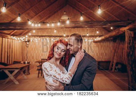 Rustic Wedding Couple Gently Hugging Under Retro Bulbs Lights In Wooden Barn. Space For Text. Newlyw
