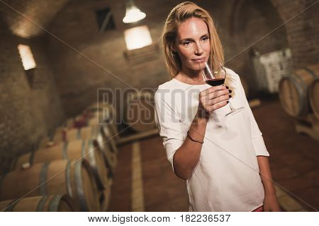 Beautiful woman oenologist tasting wine in winegrower cellar