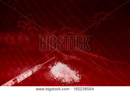 teen arrested with drug narcotic addict concept young women in cage or jailed sad hopeless in prison no freedom from heroin drug liquid in syringe with powder.