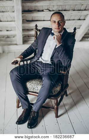 Stylish Groom Portrait On Background Of White Wooden Wall. Rustic Wedding Concept In Barn, Space For