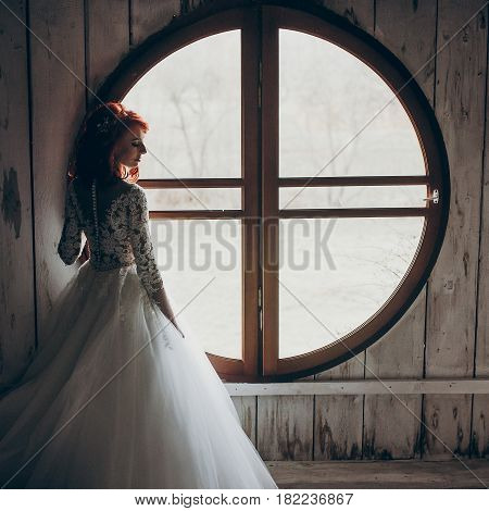 Stylish Bride Posing At Round Window In Light On Background Of White Wooden Wall. Rustic Wedding Con