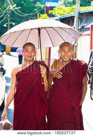 YANGON, MYANMAR-MARCH 2, 2017: Two unidentified young monks walking under the umbrella in Yangon, Myanmar on March 2, 2017.