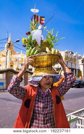 YANGON, MYANMAR -MARCH 3, 2017: Woman wears on his head baskets of green bananas and coconuts for donation at Botataung Pagoda in Yangon, Myanmar. (Burma)