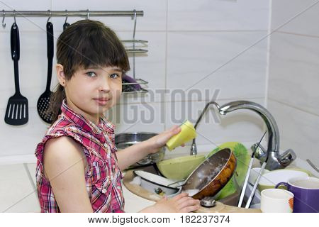 The child washes a bunch of dirty dishes standing near the sink and smiling