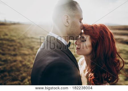 Stylish Bride And Groom Embracing In Sunlight In Mountains At Sunset Light. Gorgeous Boho Newlywed C