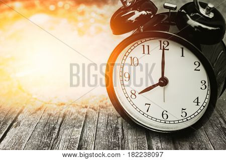 old memory time concept retro clock timed at 8 o'clock on wood with sun light.