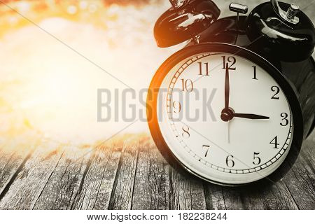 Old Memory Time Concept, Retro Clock Timed At 3 O'clock On Wood With Sun Light.