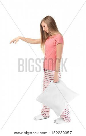 Young sleepy woman with pillow suffering from somnambulism on white background