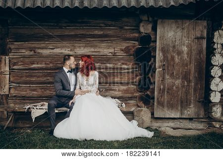 Stylish Groom And Happy Bride Sitting On Bench At Wooden House In Evening. Rustic Wedding  In Barn C