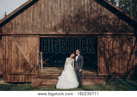 Rustic Wedding Couple Posing And Standing At Background Of Wooden Barn. Wedding Concept, Space For T