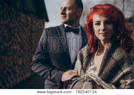 Stylish Groom And Happy Bride In Blanket Hugging In Light On Background Of Wooden Firewood Wall. Rus