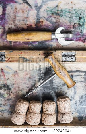Vintage corkscrew with a wooden handle and wine corks lying in a wooden box painted in different colors . vertical frame