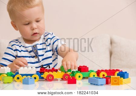 Toddler boy playing with colorful plastic bricks at the table. Toddler having fun and building out of bright constructor bricks. Early learning. stripe background. Developing toys