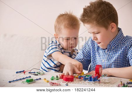 Portrait of cute kid boy and his toddler brother playing with electronic constructor and game at the desk at home. Children learning.