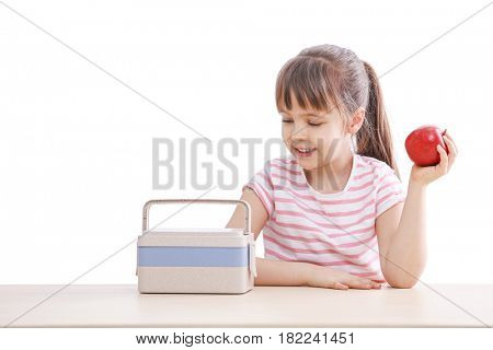 Happy schoolgirl with lunch box and apple at table on white background