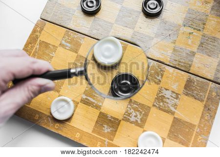 Checkers game under the magnifying glass. White and black checkers on an old shabby chessboard. Logic and strategy of business concept