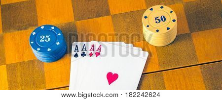Winning combination of playing cards in poker four aces on a chessboard plastic chips are the monetary equivalent for winning the game then you can change them for money
