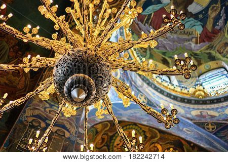 ST. PETERSBURG, RUSSIA - MARCH 21, 2015: Interior of St. Isaac's Cathedral with vintage iron chandelier with floral twisted ornament gold color close-up.