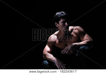 The muscle man is crouched down showing his muscle.