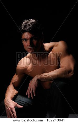 The handsome man is crouched down looking buff.