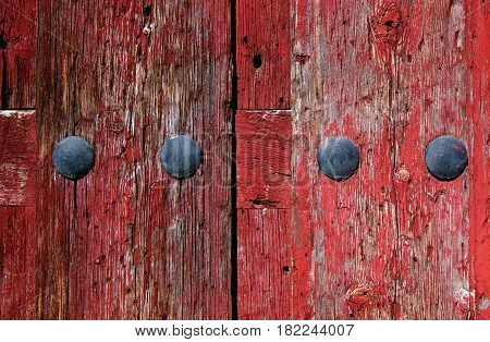 Old Red Cracked Wooden Background with Rivets closeup Outdoors